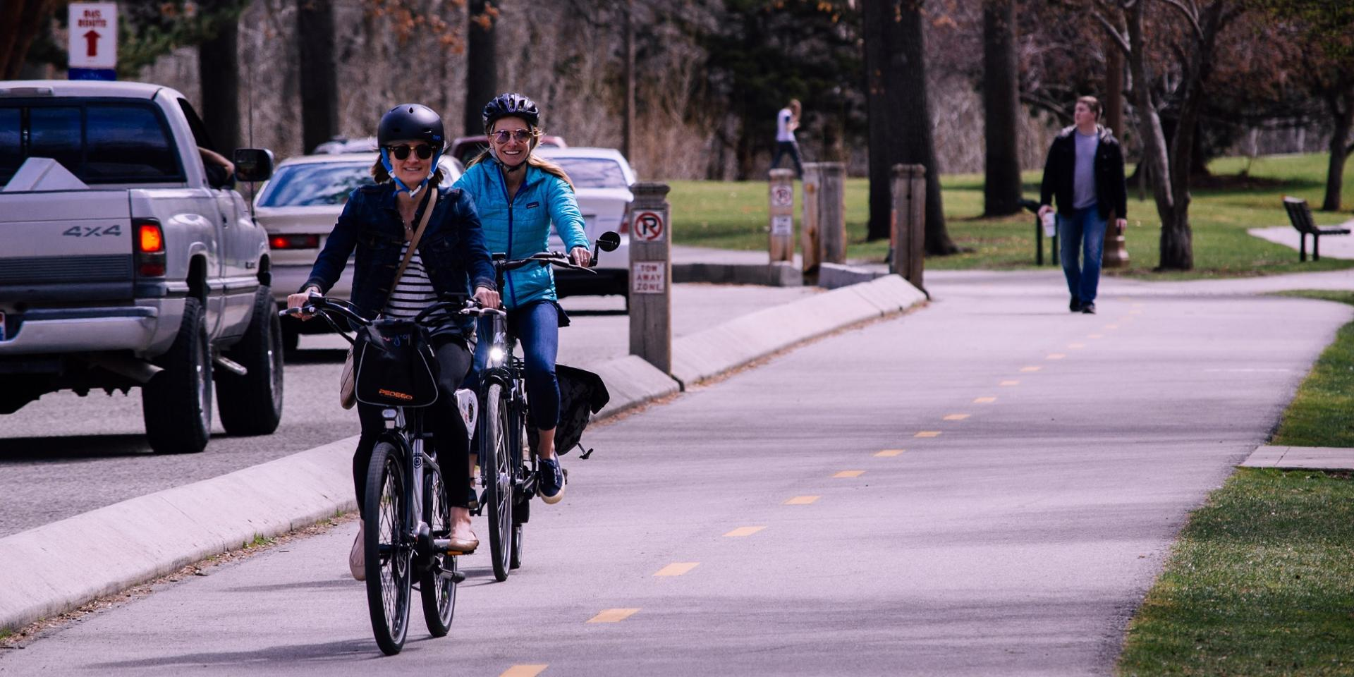 Two women riding bicycles on a bike path