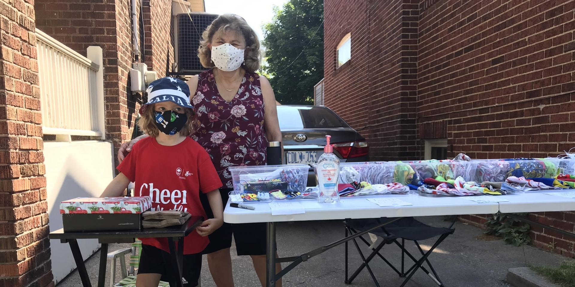 woman and boy standing next to table of masks