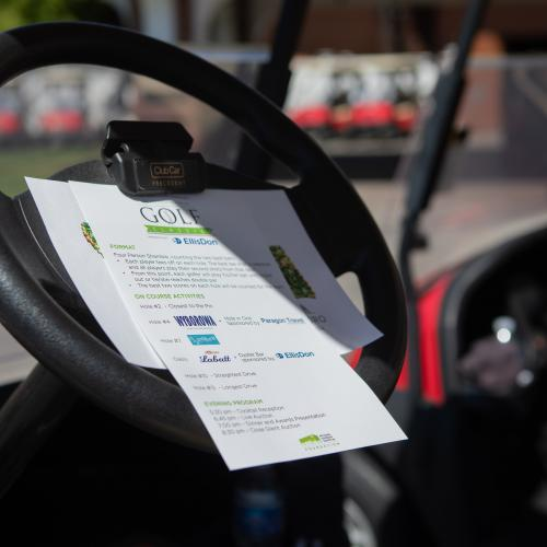 close up shot of golf cart steering wheel with score sheet attached