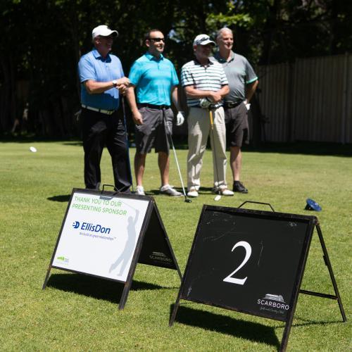 Four golfers in background, EllisDon sponsor board and Hole 2 board in foreground