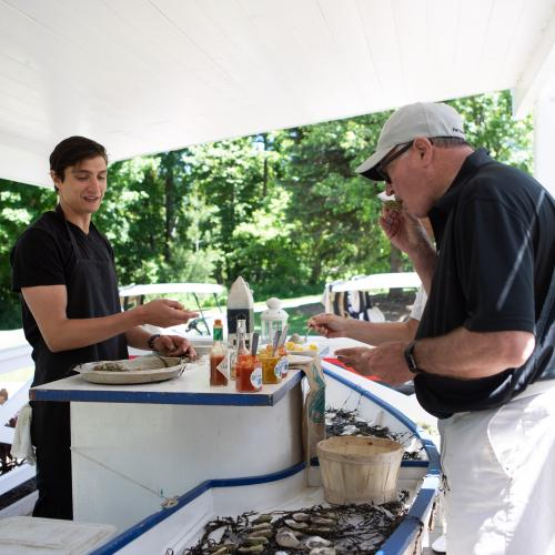 Golfers sampling oysters at oyster stand