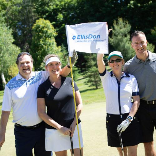 Four golfers facing camera, holding EllisDon sponsor flag