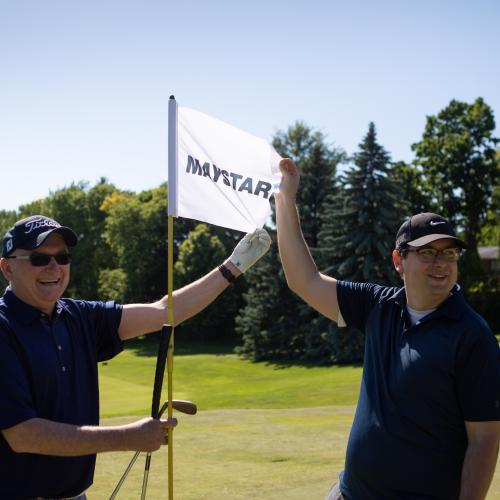 two men standing holding MayStar sponsor flag