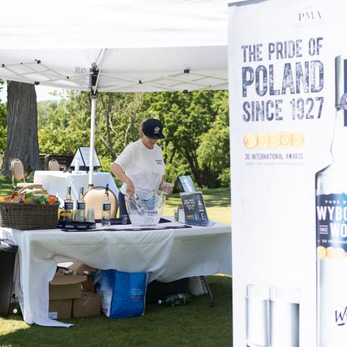 white tent with table and bottles of Wyborowa vodka, with server behind
