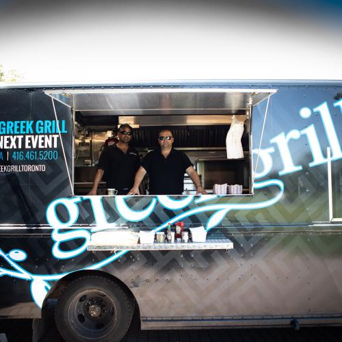 two men looking out window of Greek Grill food truck