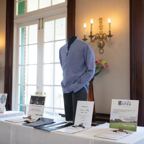 view of silent auction table with different auction item placards and a mannequin wearing shirt