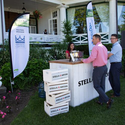 two men standing at Stella Artois beer stand with server on clubhouse grounds