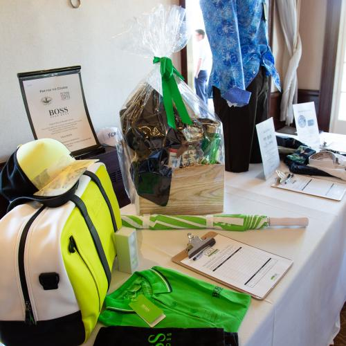 close up view of auction items on table including duffel bag, gift basket and mannequin with shirt