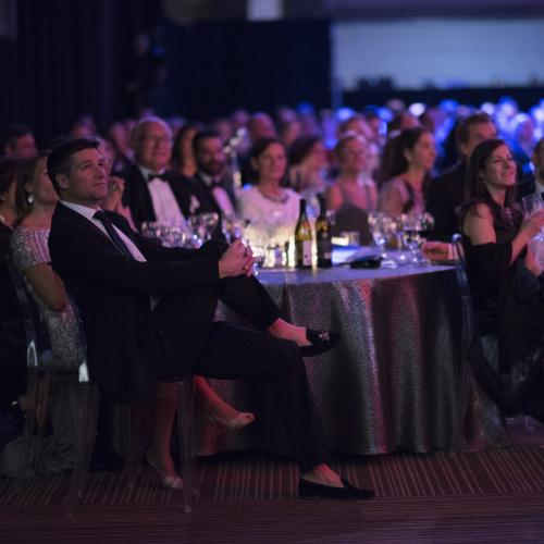 people sitting at tables for gala event dark lit room