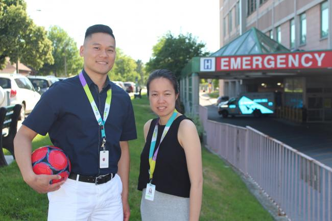 Andrew Liu, Clinical Manager, Pharmacy and Grace Ho, Pharmacist pictured with a soccer ball outside the Michael Garron Hospital Emergency Department