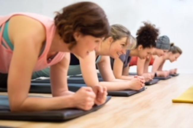 several women in fitness class lying down on forearms