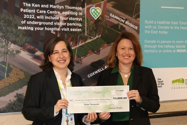 two woman holding a large cheque