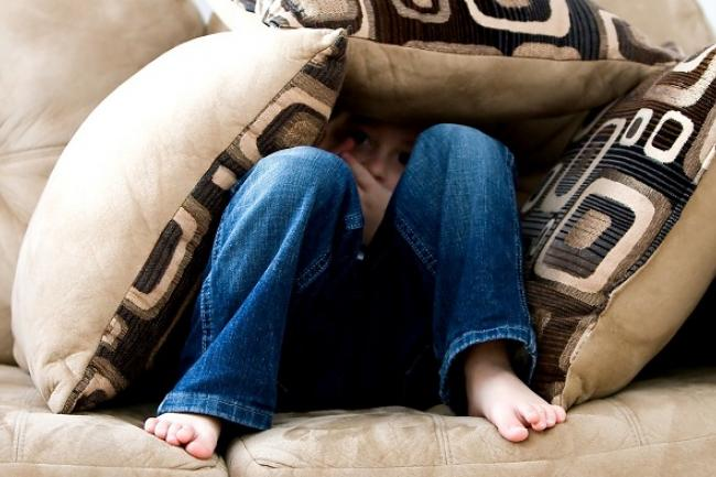 little boy sitting on couch with knees up looking ahead mostly covered up with throw cushions