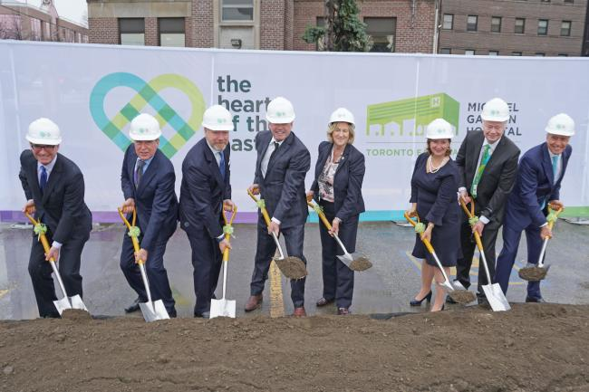 executives pose with shovels in front of HOTE banner